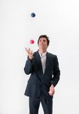 Juggling businessman. A young businessman deftly juggles three colored balls in front of a white background Royalty Free Stock Photo