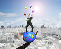 Juggling businessman standing on symbols ball balancing on wire Royalty Free Stock Photography