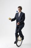 Juggling businessman on unicycle Stock Photos