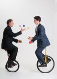 Juggling businessmen riding unicycles Royalty Free Stock Photos