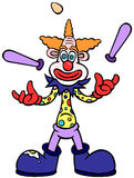 Juggling Clown. A skinny orange haired clown wearing a spotted clown shirt, red gloves and large boots and juggling two batons and an egg Royalty Free Stock Photography