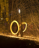 Juggling with fire in pair. Pair of young people juggling with fire and creating fire circles and sparks all around Stock Images