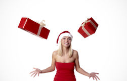 Juggling Presents. Cheerful Blond Santa Girl Juggling With Presents Royalty Free Stock Photos