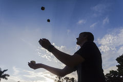 Juggling Teenager Silhouetted. Juggling small bean bags ,male teenager silhouetted against blue sky and cirrus clouds Royalty Free Stock Image