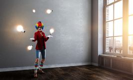 Juggling woman clown . Mixed media. Woman with clown make up wearing wig juggling items . Mixed media royalty free stock image