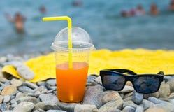 Jugo con la paja de beber y las gafas de sol en la playa cerca del mar Foto de archivo