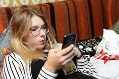 Jugo de consumición adolescente y mirada de smartphone Fotos de archivo libres de regalías