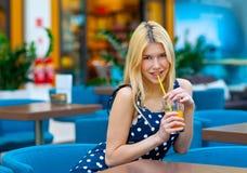 Jugo de consumición de la muchacha adolescente atractiva en barra Fotografía de archivo