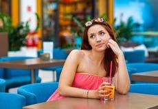 Jugo de consumición de la muchacha adolescente atractiva en barra Fotografía de archivo libre de regalías