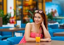 Jugo de consumición de la muchacha adolescente atractiva en barra Imagen de archivo libre de regalías