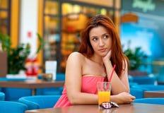 Jugo de consumición de la muchacha atractiva en barra Foto de archivo libre de regalías