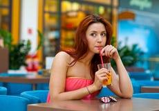 Jugo de consumición de la muchacha atractiva en barra Fotografía de archivo libre de regalías