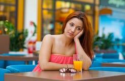 Jugo de consumición de la muchacha triste atractiva en barra Foto de archivo