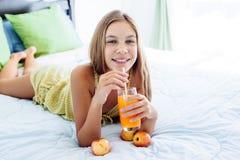 Jugo de consumición de la muchacha y relajación en dormitorio Fotografía de archivo libre de regalías