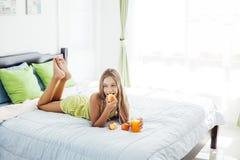 Jugo de consumición de la muchacha y relajación en dormitorio Imagen de archivo libre de regalías