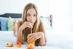Jugo de consumición de la muchacha y relajación en dormitorio Imagenes de archivo