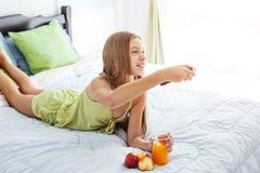 Jugo de consumición de la muchacha y TV de observación en dormitorio Foto de archivo libre de regalías