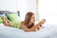 Jugo de consumición de la muchacha y TV de observación en dormitorio Fotografía de archivo libre de regalías
