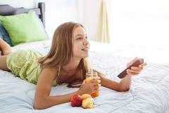 Jugo de consumición de la muchacha y TV de observación en dormitorio Imagen de archivo
