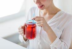 Jugo de consumición de la mujer de la taza de cristal con la paja Foto de archivo