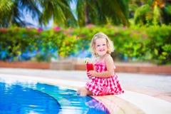 Jugo de consumición de la niña en una piscina Imagenes de archivo
