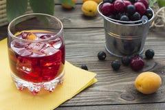 Jugo de la cereza con la fruta en un cubo Imágenes de archivo libres de regalías