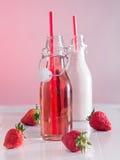 Jugo de la fresa y leche de la fresa en botellas Fotografía de archivo libre de regalías