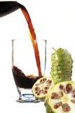 Jugo de la fruta de Noni que fluye en el vidrio de cóctel Fotografía de archivo libre de regalías