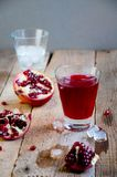 Jugo de la granada con hielo y fruta en la tabla de madera Bebida de restauración del verano Foto de archivo libre de regalías