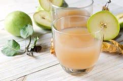Jugo de la pera con las frutas frescas en el fondo de madera blanco Imagen de archivo