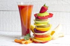Jugo de la primavera y pila frescos de frutas y verduras de la rebanada Imagen de archivo
