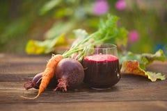 Jugo de la Remolacha-zanahoria en vidrio en la tabla Foto de archivo libre de regalías