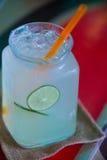 Jugo de limón frío delicioso en vidrio y cales con la paja anaranjada imagen de archivo