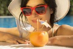 Jugo de pomelo de consumición femenino joven en la piscina Imagenes de archivo