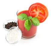 Jugo de tomate con las hojas de la albahaca, la rebanada del tomate y los cuencos con pimienta negra y sal del mar Foto de archivo libre de regalías