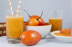 Jugo de tomate de árbol. Un vaso con jugo de tomate de árbol codeado de la fruta Stock Images