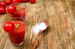Jugo de tomate en dos vidrios y tomates Imagenes de archivo