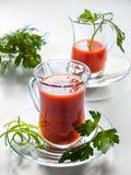 Jugo de tomate en las tazas de cristal en las placas de cristal Imágenes de archivo libres de regalías