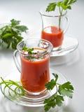 Jugo de tomate en las tazas de cristal en las placas de cristal Fotografía de archivo