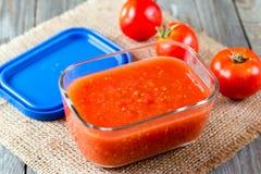 Jugo de tomate en un envase de cristal en una tabla Fotografía de archivo