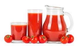 Jugo de tomate en vidrios y tomates frescos Imagen de archivo