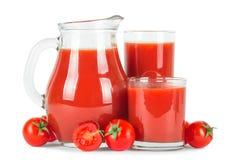Jugo de tomate en vidrios y tomates frescos Fotos de archivo