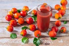 Jugo de tomate fresco con el tomate en piso de madera fotos de archivo