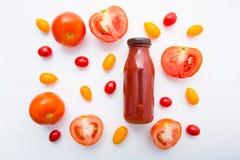 Jugo de tomates en botella y rebanadas frescas de los tomates en la madera blanca Foto de archivo libre de regalías