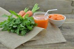 Jugo de zanahoria con las zanahorias de las rebanadas en cuenco en la tabla de madera Imágenes de archivo libres de regalías
