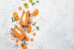 Jugo de zanahoria o smoothies con las semillas de lino en las botellas de cristal, bebida del vegano, bebida sana para la dieta c foto de archivo