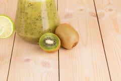 Jugo del kiwi en el escritorio de madera Fotos de archivo