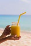 Jugo del mango de la vitamina en un tubo de cristal con una naranja en su mano en el fondo del mar de la turquesa en las zonas tr Fotografía de archivo