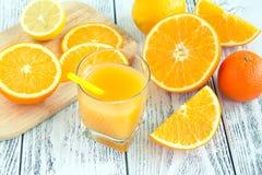 jugo en el vidrio de la naranja y del limón en un fondo rústico Foto de archivo