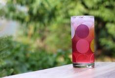 Jugo frío, rosado con hielo en una taza de cristal del descenso en un de madera en el fondo verde del jardín Fotos de archivo